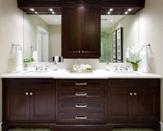 Un baño con muebles de madera oscura se ilumina estratégicamente